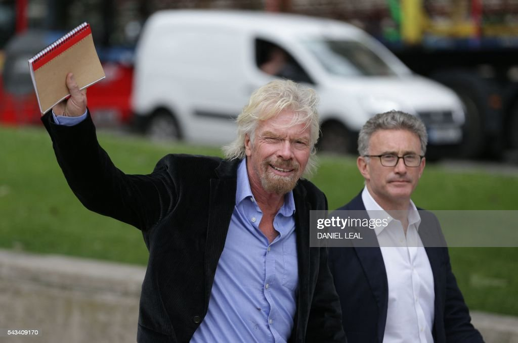 British entrepreneur Richard Branson (L) waves as he walks by the Houses of Parliament in central London on June 28, 2016. Branson, head of the Virgin Group said today that the company has lost about a third of its value since the UK voted to leave the European Union. / AFP / DANIEL