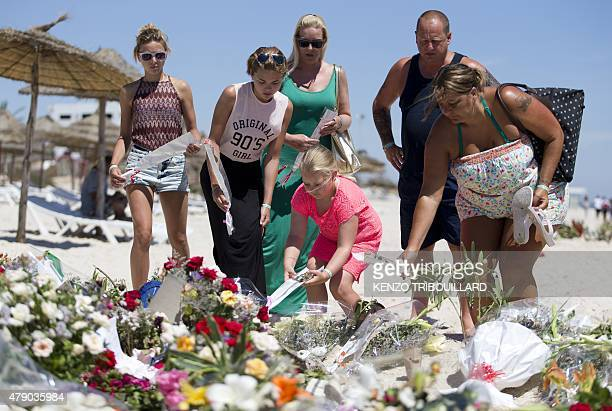 A British family who witnessed the beach massacre by a jihadists gunman the previous week lay flowers at the site of the attack on the beach in front...