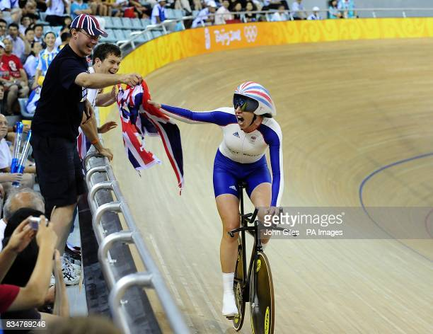 A British fan hands Britain's Rebecca Romero the Union Flag as she rides past during her celebrations after winning the gold medal in the women's...
