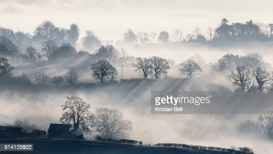 British farmland valley scene at daybreak with mist and light rays