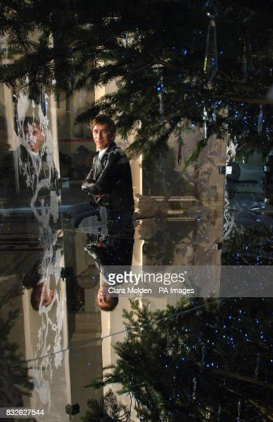 British fashion and homeware designer Jasper Conran sits next to the Christmas tree he has designed for the Grand Entrance of the Victoria and Albert...