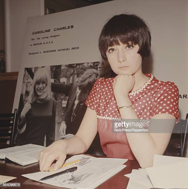British fashion designer Caroline Charles pictured sitting with sketches and notebooks in London circa 1965