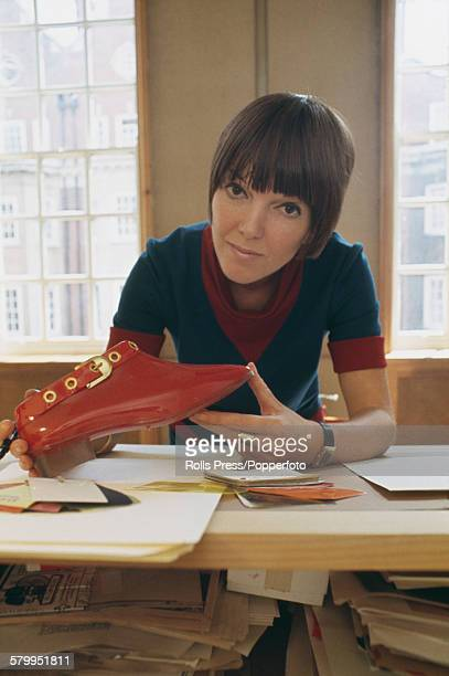 British fashion designer Mary Quant pictured holding a red patent leather buckle shoe at a drawing table in her design studio in London in 1967