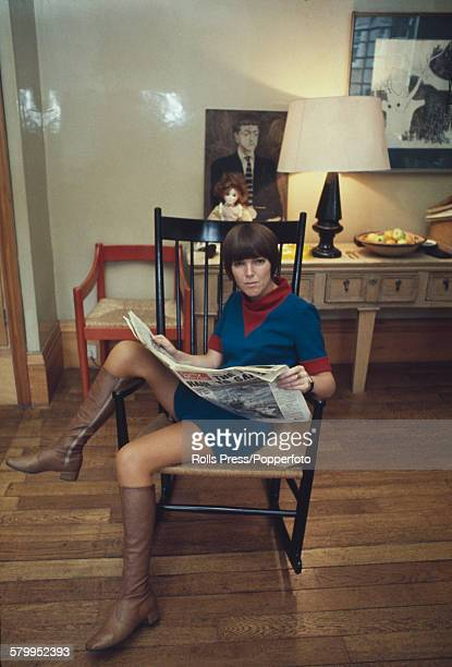British fashion designer Mary Quant pictured reading the Daily Mirror newspaper in a rocking chair at home in London in 1967