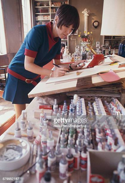 British fashion designer Mary Quant pictured working at a drawing board and creating ideas for possible shoe and footwear designs in her design...