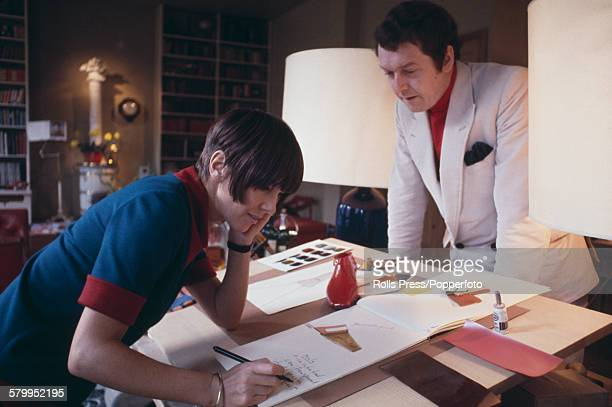 British fashion designer Mary Quant pictured working on sketches for shoes and footwear at a drawing table with her husband Alexander Plunket Greene...