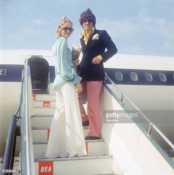British fashion model Twiggy and her partner and manager Justin de Villeneuve board a BEA aircraft at London Airport for a holiday in Greece 24th...