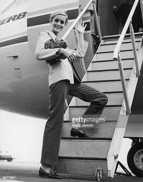 British fashion model Twiggy boards an aircraft at Heathrow bound for Tunisia on an export drive for Berkertex 28th September 1966