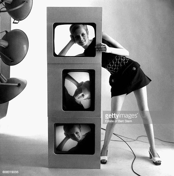 British fashion model Twiggy looking through a cut out above television screens showing images of her face in a shoot for Vogue Magazine Paris 1967