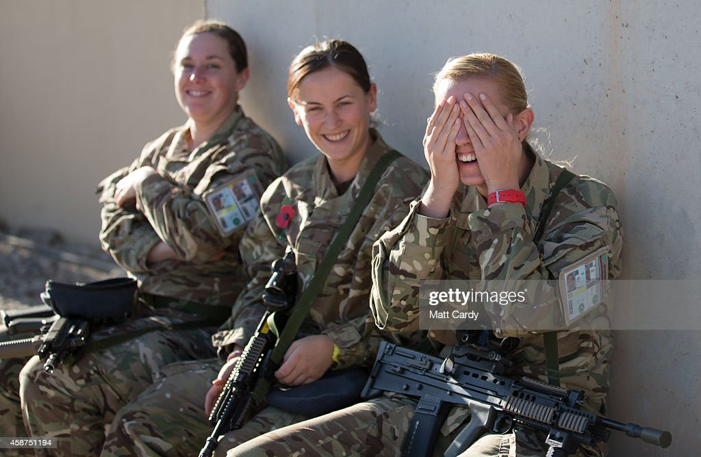 British female troops share a joke as they wait for the 904 Expeditionary Air Wing's sunset flag lowering and end of mission ceremony at Kandahar...
