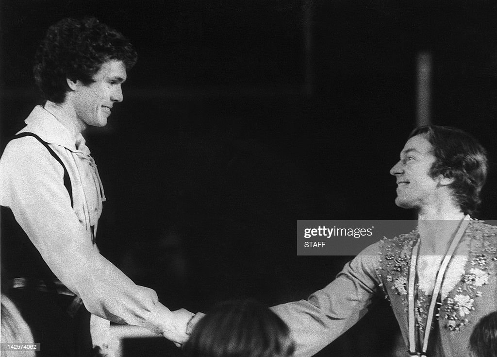 British figure skater John Curry (L) shakes hands with Canadian <a gi-track='captionPersonalityLinkClicked' href=/galleries/search?phrase=Toller+Cranston&family=editorial&specificpeople=2621539 ng-click='$event.stopPropagation()'>Toller Cranston</a> on the podium of the men's figure skating 11 February 1976 in Innsbruck at the Winter Olympic Games. Curry won the gold medal in front of Russian Vladimir Kovalev (silver) and Cranston (bronze).