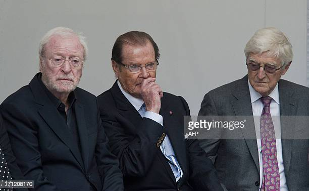 British film actors Michael Caine and Roger Moore sit beside British TV presenter Michael Parkinson at a memorial to the late film director and...