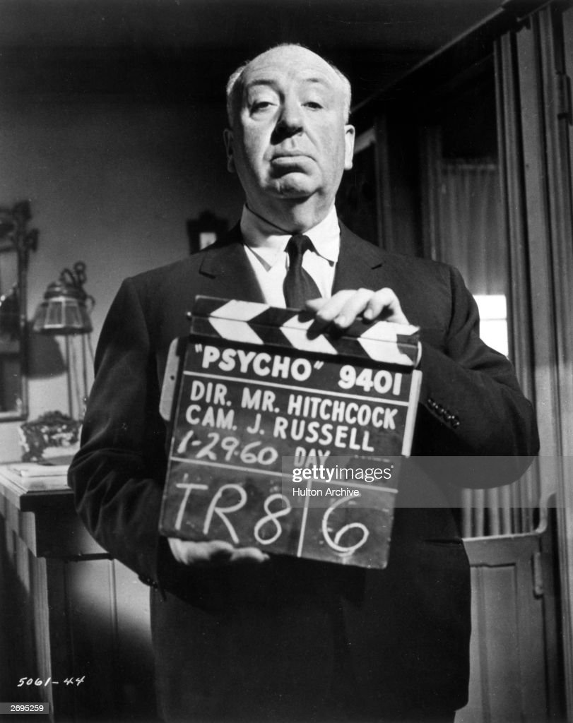 Portrait of Alfred Hitchcock holding up a clapperboard on the set of the film Psycho