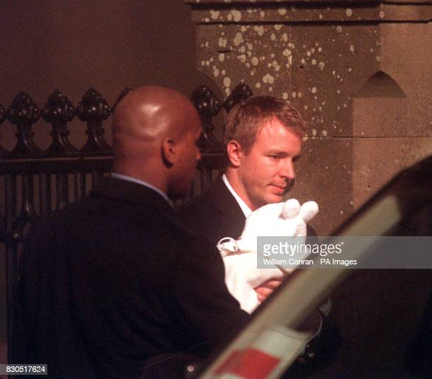 British film director Guy Ritchie with his and Madonna's fourmonthold baby son Rocco wrapped in a white christening gown after the baby was...