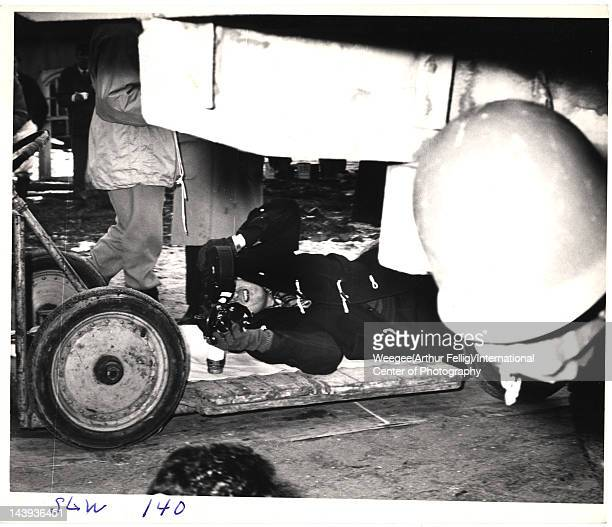 British film director Stanley Kubrick hangs under a trucks looks through a camera during the filming of 'Dr Strangelove Or How I Learned to Stop...