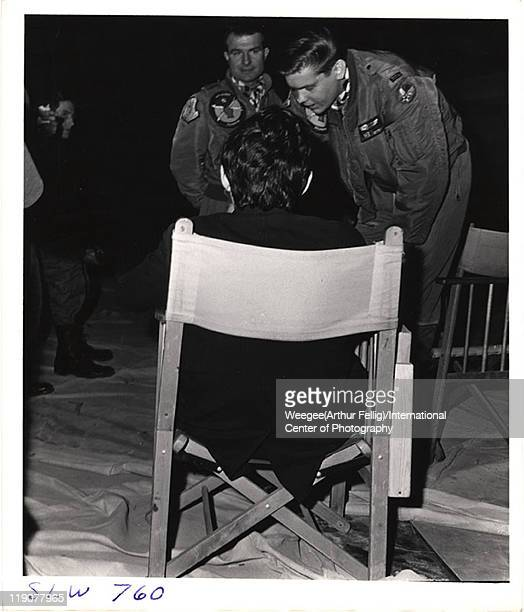 British film director Stanley Kubrick speaks with two unidentified actors during the filming of his movie 'Dr Strangelove Or How I Learned to Stop...
