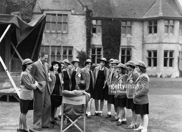 British filmmaker Frank Launder with actor Guy Middleton and a group of schoolgirl extras at Langley Court Liss Hampshire during filming of the...