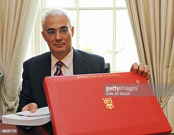 British Finance Minister Alistair Darling poses for pictures with a copy of the 2009 Budget report and the red briefcase that traditionally holds the...
