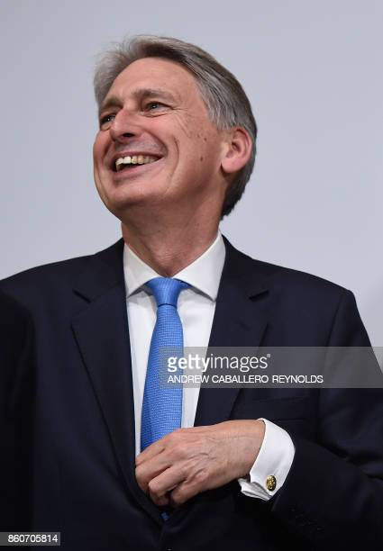 British Finance Minister Philip Hammond laughs before the G20 Finance ministers group photo at the IMF headquarters in Washington DC on October 12...
