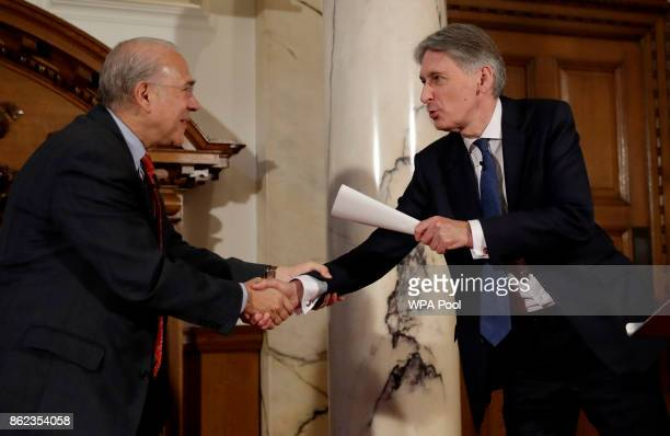 British Finance Minister Philip Hammond shakes hands with the SecretaryGeneral of the Organisation for Economic Cooperation and Development Angel...