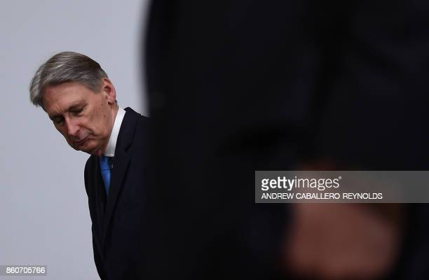 British Finance Minister Philip Hammond tries to find his place to stand on the stage for the G20 Finance ministers group photo at the IMF...