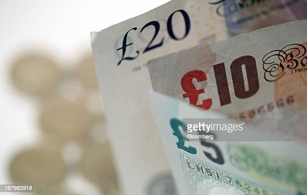 British five 10 and 20 pound notes stand near a pile of one pound coins in this arranged photograph taken in London UK on Thursday Nov 14 2013 The...
