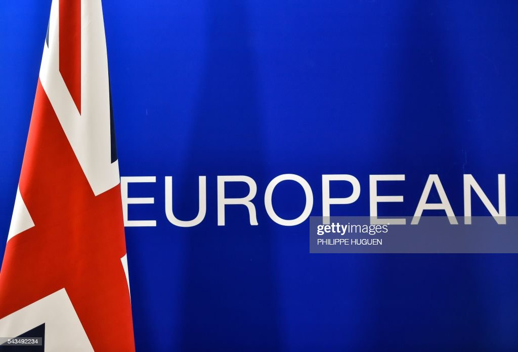 A British flag is seen next to the word 'European', during a press conference of British Prime minister during an European Union summit on June 28, 2016 at the EU headquarters in Brussels. Britain's exit from the European Union may erode the bloc's leadership role in fighting climate change and stymie crucial efforts to set more ambitious targets for cutting greenhouse gases, officials and experts said on June 28. European leaders meeting in Brussels pressured British Prime Minister David Cameron Tuesday to launch the two-year withdrawal process 'as soon as possible', but the embattled premier has vowed he will leave that task to a successor to be named on September 9. / AFP / PHILIPPE