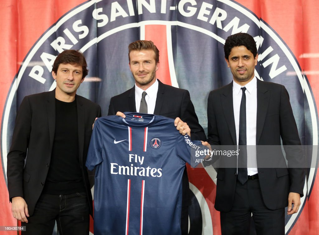British football player David Beckham, flanked by PSG Qatari president Nasser Al-Khelaifi (L) and Brazilian sport director Leonardo, poses with his new Paris Saint-Germain (PSG) jersey at the end of a press conference, on January 31, 2013 at the Parc des Princes stadium in Paris. Beckham signed a five-month deal with the Ligue 1 leader until the end of June.
