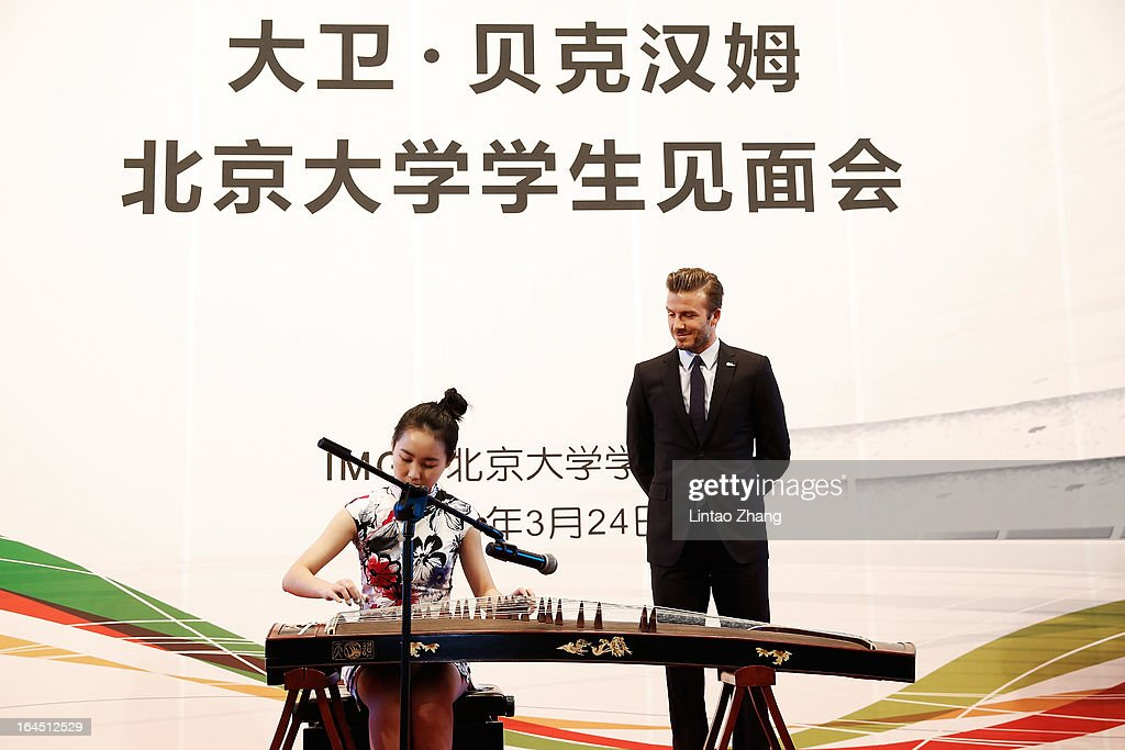 British football player David Beckham learns to play Chinese musical instruments during a visit to Peking University on March 24, 2013 in Beijing, China. David Beckham is on a five-day visit to China at the invitation of the China Football Association as China's first international ambassador.