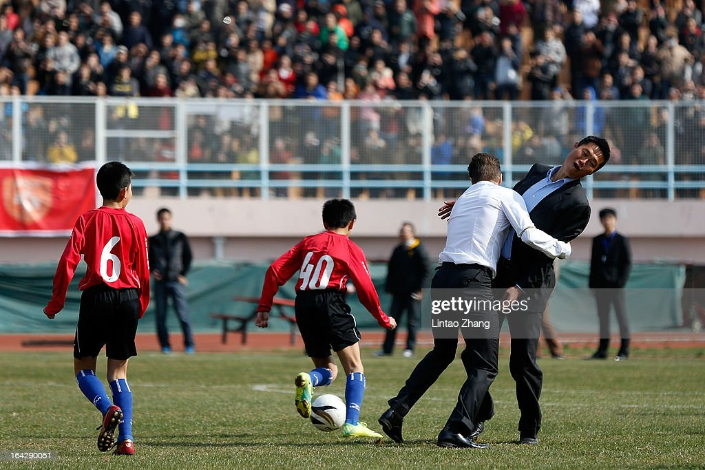 British football player <a gi-track='captionPersonalityLinkClicked' href=/galleries/search?phrase=David+Beckham&family=editorial&specificpeople=158480 ng-click='$event.stopPropagation()'>David Beckham</a> plays with Su Maozhen (R) during a training session with Qingdao youth team at Tiantai Stadium, Shandong Province on March 22, 2013 in Qingdao, China. <a gi-track='captionPersonalityLinkClicked' href=/galleries/search?phrase=David+Beckham&family=editorial&specificpeople=158480 ng-click='$event.stopPropagation()'>David Beckham</a> is on a five-day visit to China at the invitation of the China Football Association as China's first international ambassador.