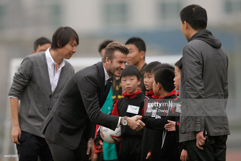 British football player David Beckham shakes hands with the Youth Football Team at Hankou Literary and Sports Center on March 23, 2013 in Wuhan, China. David Beckham is on a five-day visit to China at the invitation of the China Football Association as China's first international ambassador.