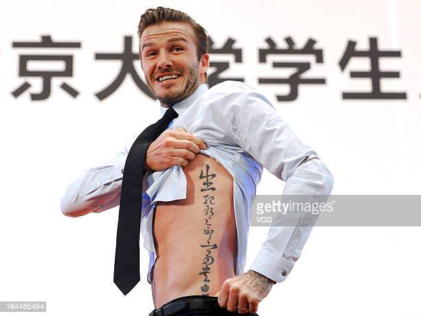 British football player David Beckham shows his tattoo to fans during his visit to Peking University on March 24 2013 in Beijing China David Beckham...