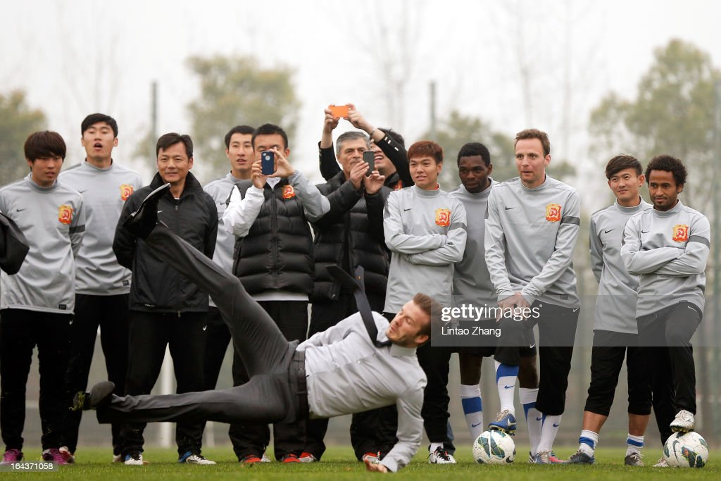British football player David Beckham slips after kicking the ball during a visit to Wuhan Zall Football Club on March 23 2013 in Wuhan China Beckham...