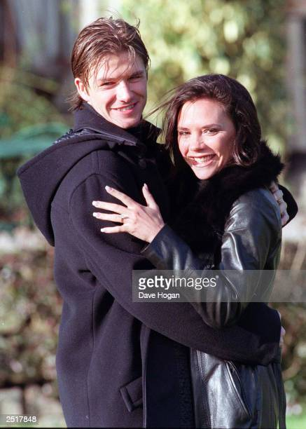 British footballer David Beckham and fiance singer from the 'Spice Girls' Victoria Adams pose for photographers outside their hotel after the...