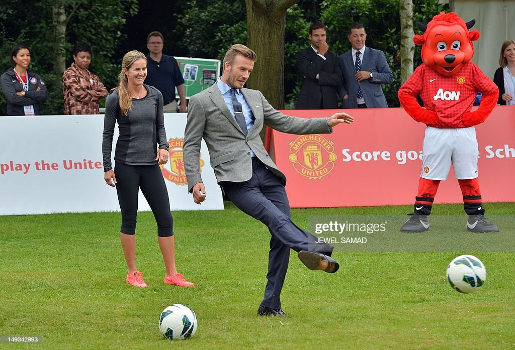 British footballer David Beckham kicks the ball during US First Lady Michelle Obama's 'Let's Move-London' event at the Winfield House in London on July 27, 2012, hours before the start of the London 2012 Olympic Games.