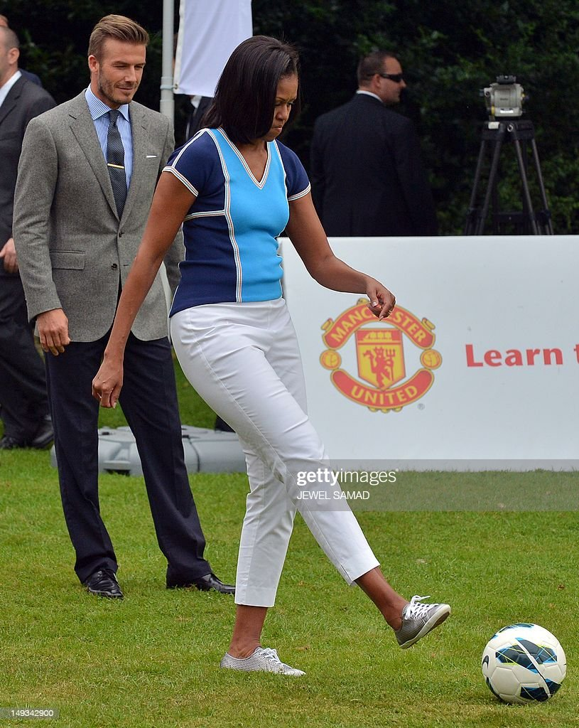 British footballer David Beckham (L) looks at US First Lady Michelle Obama kicks a ball during 'Let's Move-London' event at the Winfield House in London on July 27, 2012, hours before the start of the London 2012 Olympic Games.