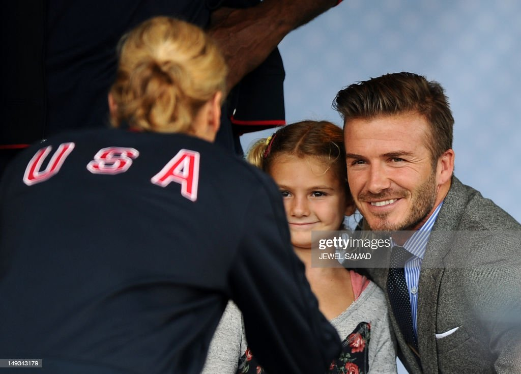 British footballer David Beckham poses on stage with the daughter of a US athlete during US First Lady Michelle Obama's 'Let's Move-London' event at the Winfield House in London on July 27, 2012, hours before the official start of the London 2012 Olympic Games.