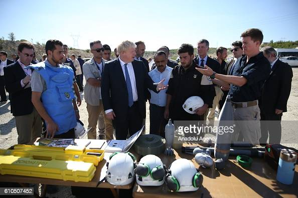 British Foreign Minister Boris Johnson is informed by Syrians who are being educated by British bomb disposal experts during his visit the container...