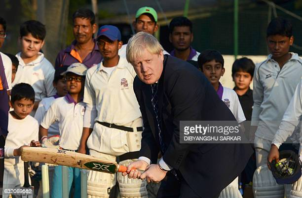 British Foreign Secretary Boris Johnson bats as he plays cricket on his visit to the Arun Lal Cricket Academy in Kolkata on January 19 2017 / AFP /...