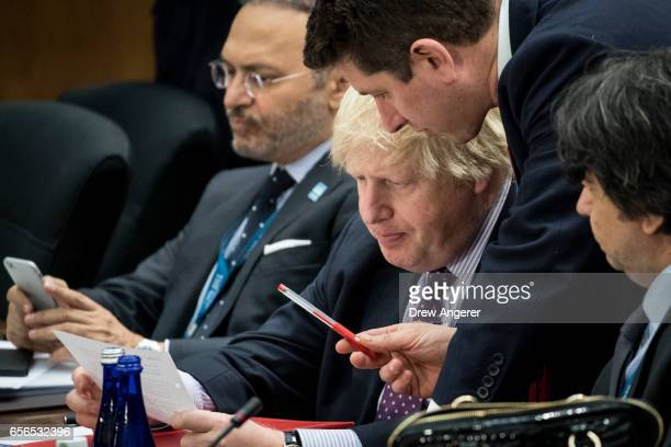 British Foreign Secretary Boris Johnson goes over notes with an aide during an afternoon working session with leaders with the global coalition...