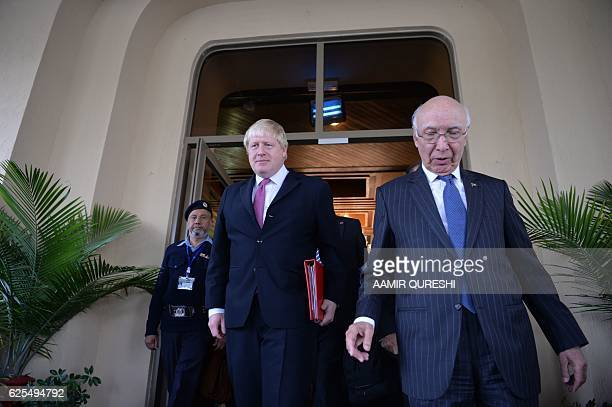 British Foreign Secretary Boris Johnson walks with Pakistan's National Security Advisor Sartaj Aziz as he leaves the Foreign Ministry in Islamabad on...