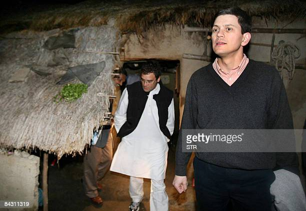 British Foreign Secretary David Miliband exits a hut while ruling Congress Party Rahul Gandhi follows during a visit to Gandhi's constituency of...