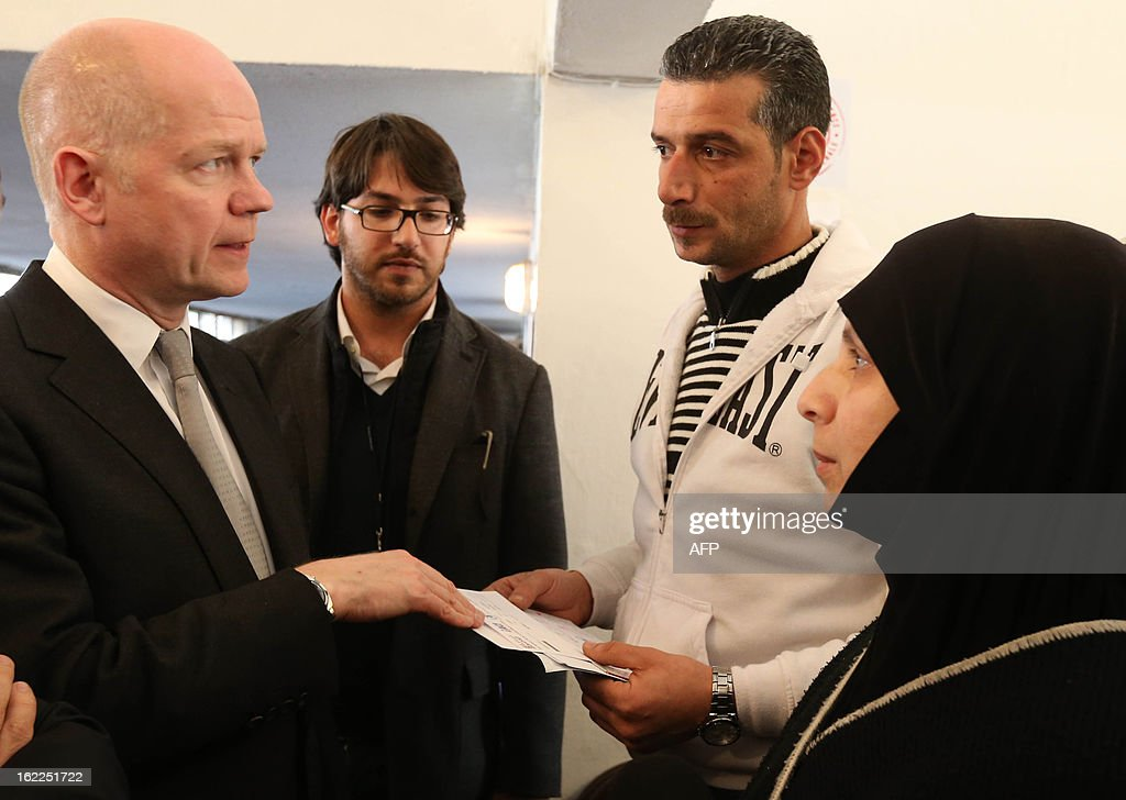 British Foreign Secretary of State for Foreign Affairs William Hague (L) talks with Syrian refugees (R and 2ndR) at a World Food Programme Center in Burj Hammoud's area on the northern outskirts of Beirut on February 21, 2013. Hague said his country would give an additional $17 million in aid money for Syrian refugees in Lebanon and expressed earlier British support for the stability of the country.