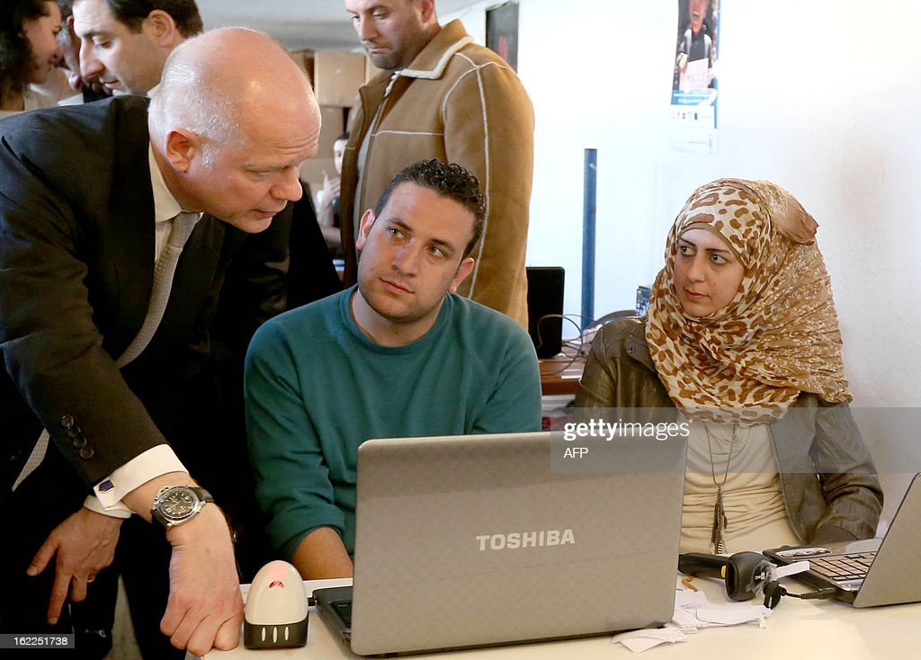 British Foreign Secretary of State for Foreign Affairs William Hague (L) chats with social workers as he inspects the registration process that Syrian refugees have to sign up for before receiving food and other aid at a World Food Programme Center in Burj Hammoud's area on the northern outskirts of Beirut on February 21, 2013. Hague said his country would give an additional $17 million in aid money for Syrian refugees in Lebanon and expressed earlier British support for the stability of the country.