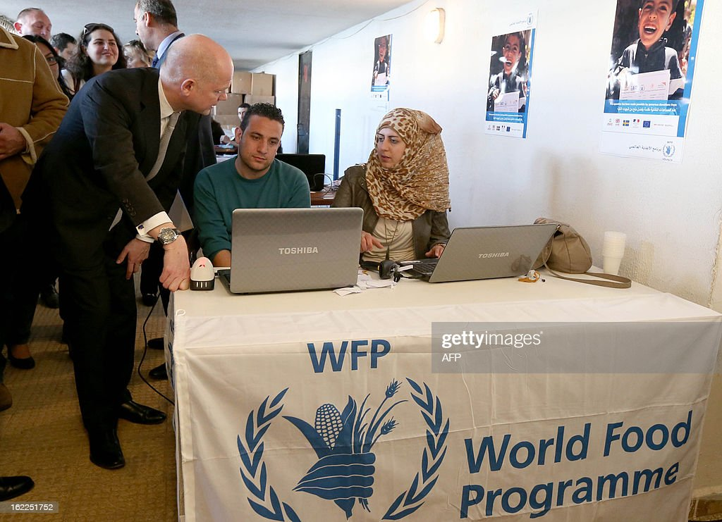 British Foreign Secretary of State for Foreign Affairs William Hague (L) chats with social workers as he inspects the registration process that Syrian refugees have to sign up for before receiving food and other aid at a World Food Programme Center in Burj Hammoud's area on the northern outskirts of Beirut on February 21, 2013. Hague said his country would give an additional $17 million in aid money for Syrian refugees in Lebanon and expressed earlier British support for the stability of the country. AFP PHOTO POOL MOMAMED AZAKIR