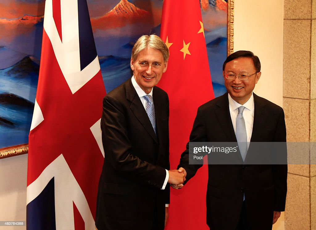 British Foreign Secretary Philip Hammond (L) and Chinese State Councilor Yang Jiechi (R) shake hands and face the media during the China-UK Strategic Dialogue held at the Diaoyutai State Guesthouse on August 13, 2015 in Beijing, China. The Chinese and British delegations are expected to hold talks to boost political and economic relations between the two countries.