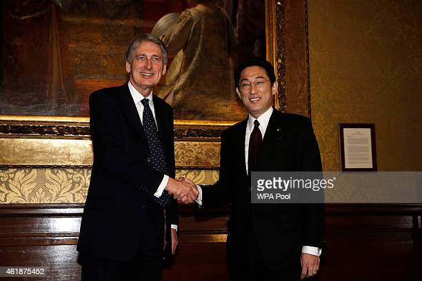 British Foreign Secretary Philip Hammond and Japanese Foreign Minister Fumio Kishida shake hands during a meeting at the Foreign and Commonwealth...