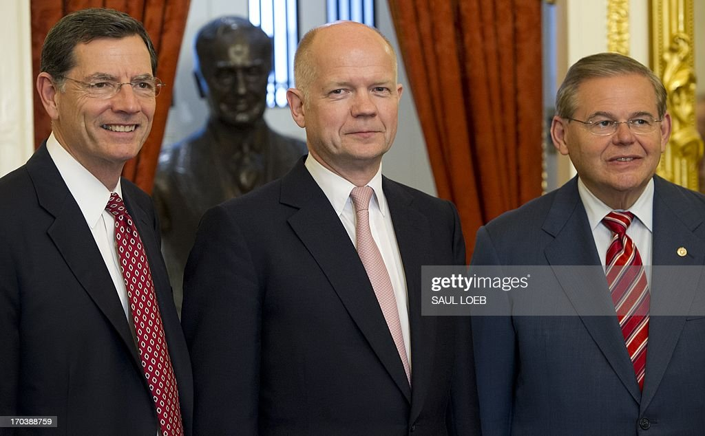 British Foreign Secretary William Hague (C) stands alongside members of the US Senate Foreign Relations committee, including committee chairman New Jersey Democrat Senator Robert Menendez (R) and Wyoming Republican Senator John Barrasso, prior to a meeting at the US Capitol in Washington, DC, June 12, 2013. AFP PHOTO / Saul LOEB