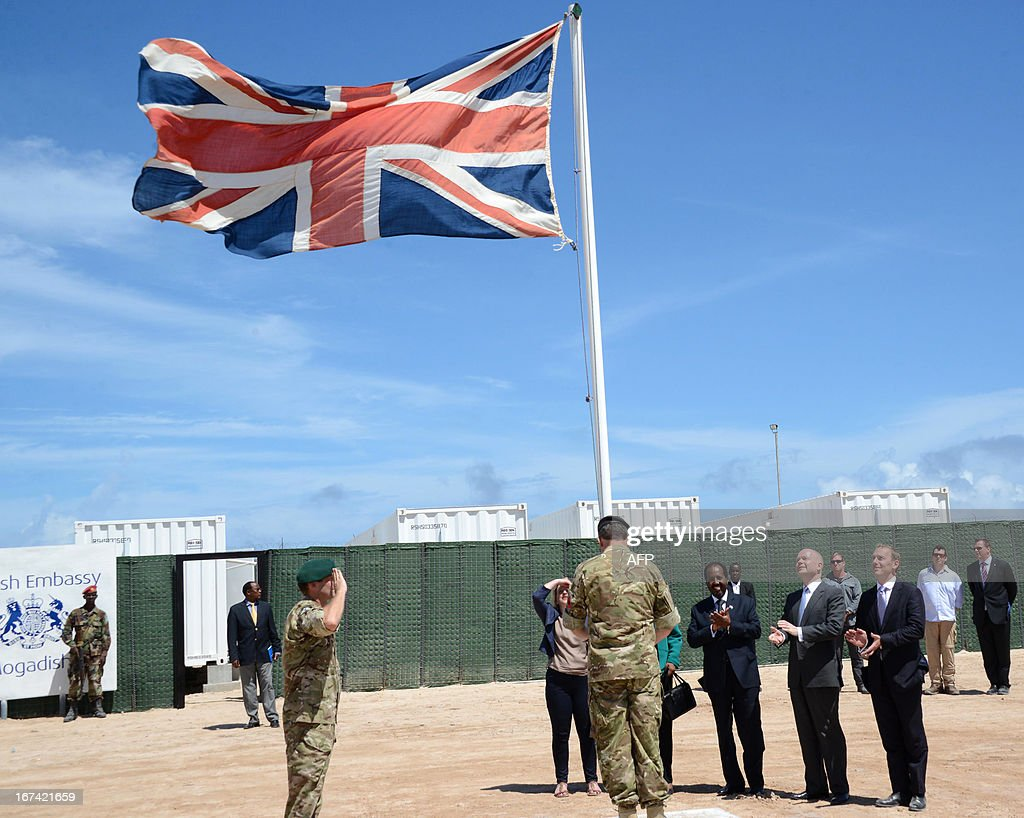 British Foreign Secretary William Hague (2nd R) stands with Somali President Hassan Sheik Mohamud (3rd R) as a British flag is raised in front of the newly opened British Embassy in Mogadishu on April 25, 2013. British Foreign Secretary William Hague opened a new embassy in Mogadishu on April 25, 22 years after London pulled its diplomats from conflict-torn Somalia. AFP PHOTO / Mohamed Abdiwahab