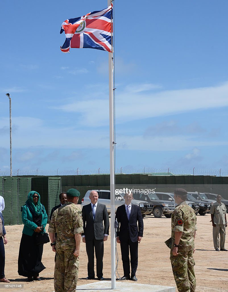 British Foreign Secretary William Hague (C) stands with Somali President Hassan Sheik Mohamud (3rd L) as a British flag is raised in front of the newly opened British Embassy in Mogadishu on April 25, 2013. British Foreign Secretary William Hague opened a new embassy in Mogadishu on April 25, 22 years after London pulled its diplomats from conflict-torn Somalia. AFP PHOTO / Mohamed Abdiwahab